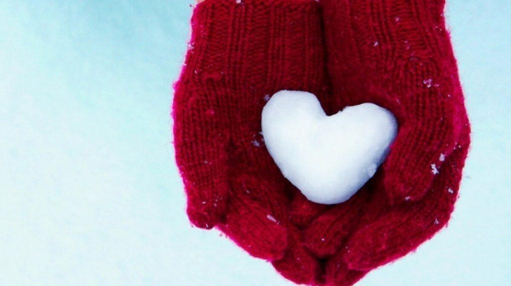 Mani con guanti e cuore