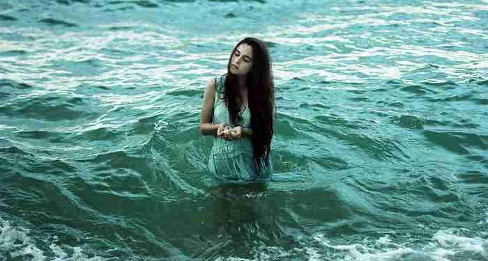 giovane ragazza cammina in mare