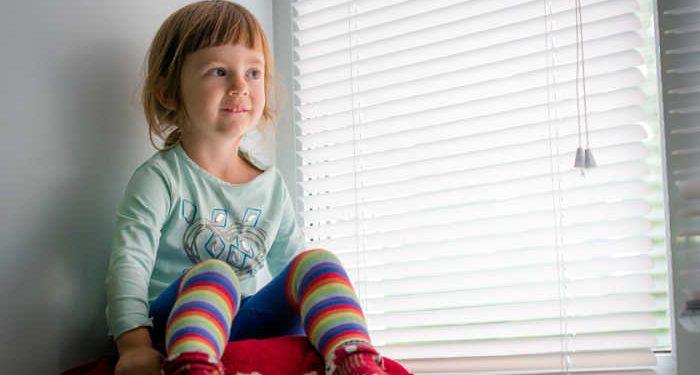 bambina dietro a finestra