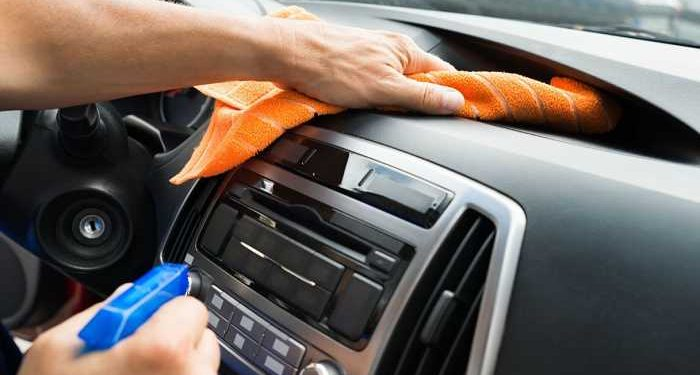 uomo pulisce interni auto