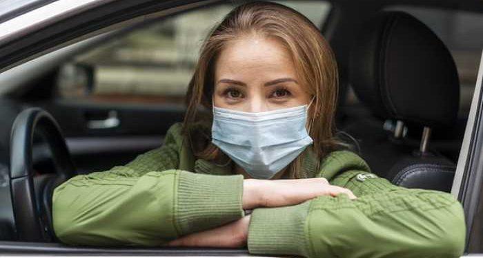 donna con mascherina in auto